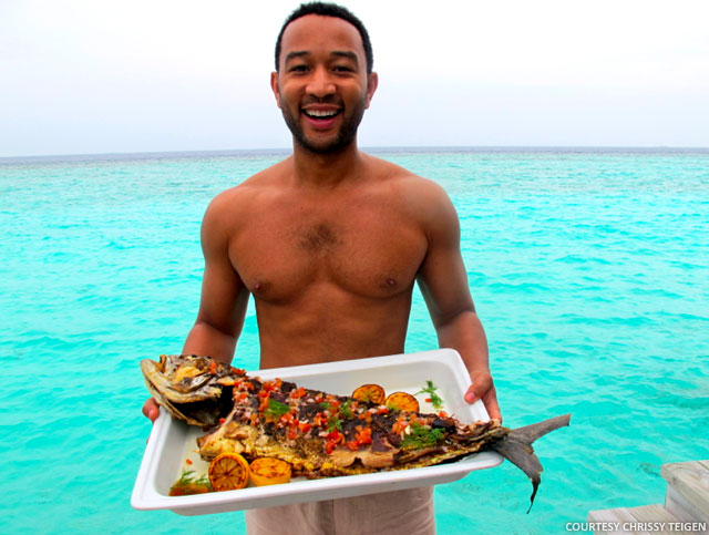 While Chrissy models on the beach, John cooks her a feast!