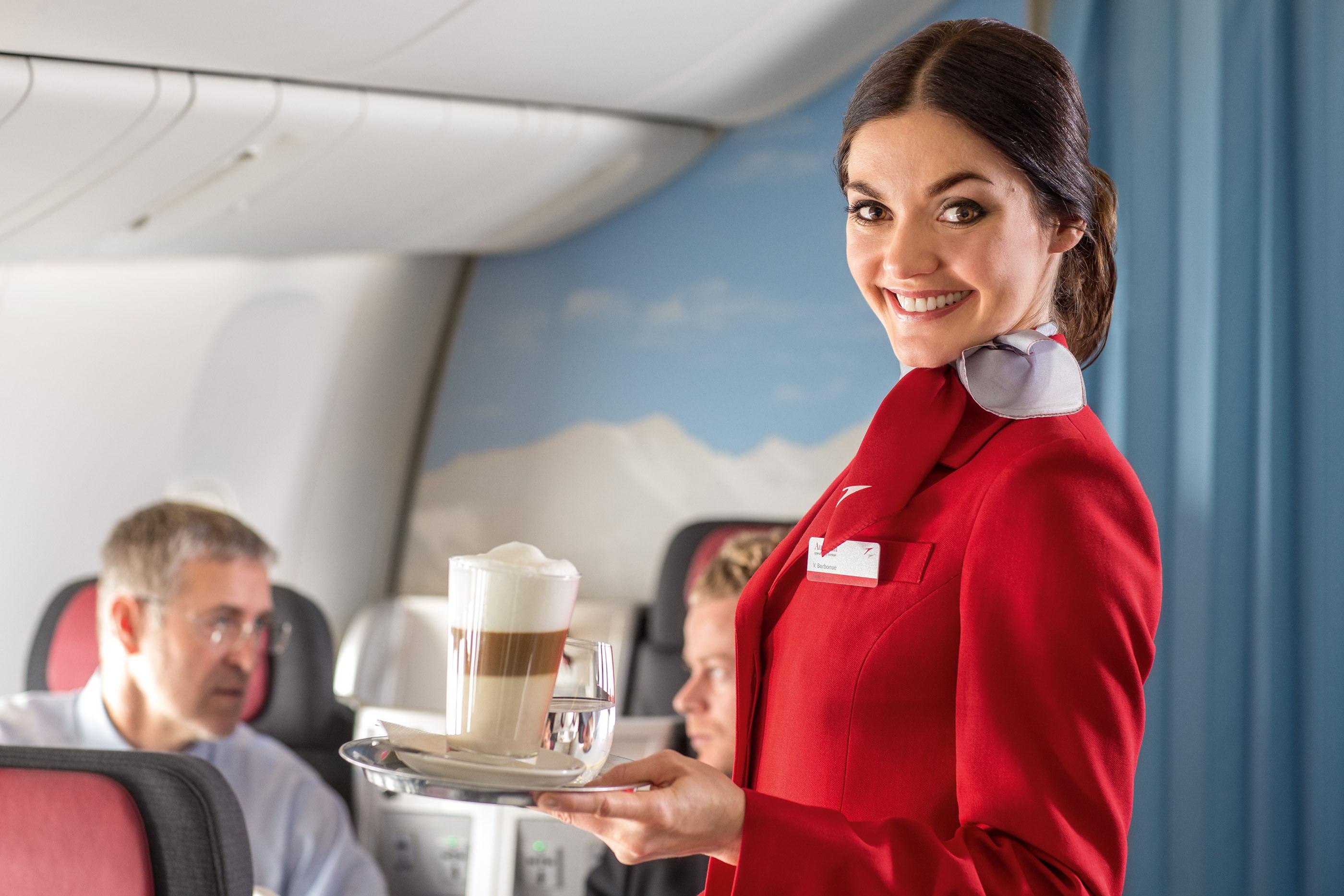 An_Austrian_Airlines_flight_attendant_serving_refreshments_to_passengers