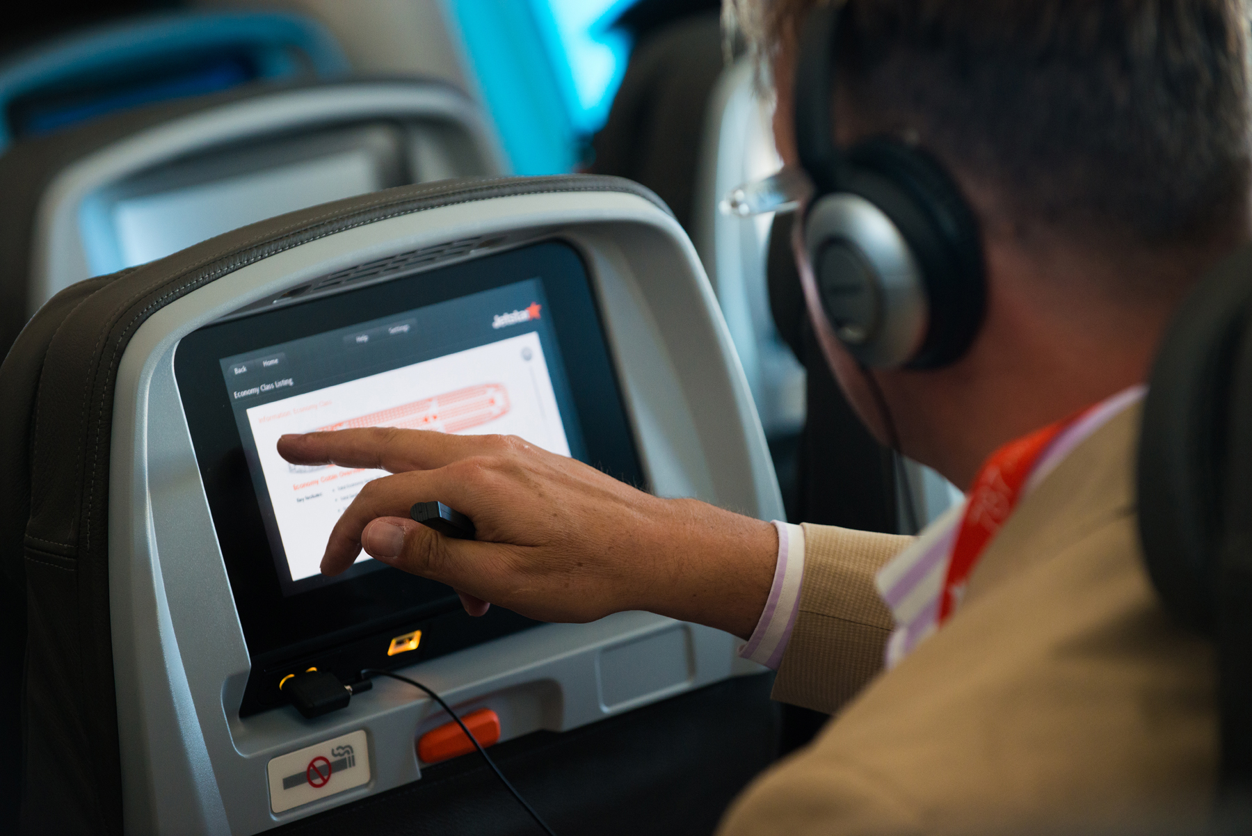 Enjoying_the_in-flight_entertainment_system_(10832720896)